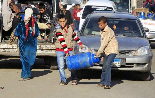 Boys carry gas cylinders to be refilled at a distribution point in Cairo January 19, 2015. (Photo by Mohamed Abd El Ghany/Reuters)