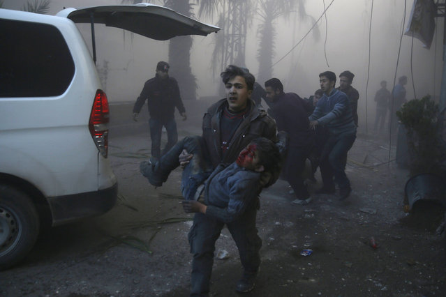 A Syrian boy carries an injured boy following reported airstrikes on the town of Hamouria in the eastern Ghouta region, a rebel stronghold east of the Syrian capital Damascus, on December 9, 2015. The Syrian Observatory for Human Rights reported at least 11 civilians, including four children, were killed in strikes on the town of Hamouria, but said it was unclear if they were carried out by Russian or regime aircraft. (Photo by Sameer Al-Doumy/AFP Photo)