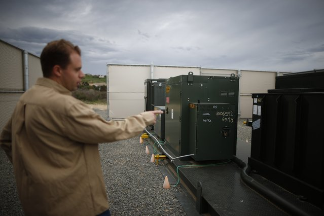 Grant Davis, an engineer at the Energy Storage Group of Advanced Technology, points out a distribution battery energy storage system in Irvine, California January 26, 2015. (Photo by Lucy Nicholson/Reuters)