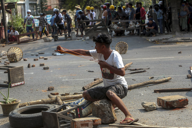 An anti-coup protester uses a sling-shot and against advancing riot policemen in Mandalay, Myanmar, Tuesday, March 2, 2021. (Photo by AP Photo/Stringer)