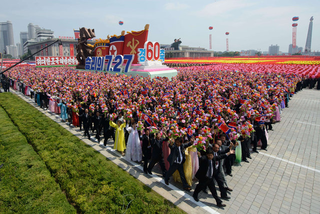 North Koreans wave flowers as they take part in a military parade past Kim Il-Sung square marking the 60th anniversary of the Korean war armistice in Pyongyang on July 27, 2013. (Photo by Ed Jones/AFP Photo)