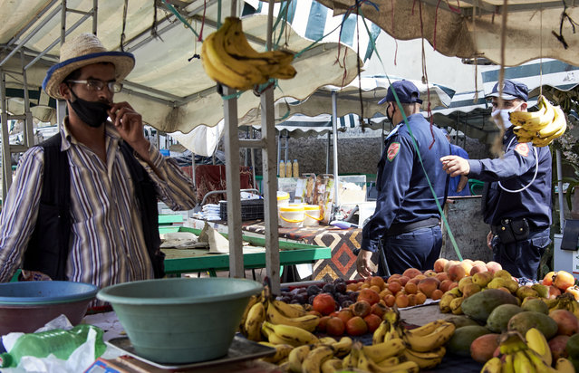 Moroccan police officers remind sellers to respect the security measures such as distancing and wearing a mask, in a market of Casablanca, Morocco, Monday, September 21, 2020. Morocco first decreed lockdown measures on March 20. Today, police checks are part of the scenery in hard-hit Casablanca, the country's economic powerhouse, or Marrakech, a major tourist destination at a standstill. (Photo by Abdeljalil Bounhar/AP Photo)