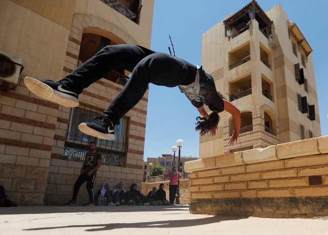 "Mariam Emad from Parkour Egypt ""PKE"" practices her parkour skills around buildings on the outskirts of Cairo, Egypt on July 20, 2018. A group of Egyptian women gather at an abandoned park in a Cairo suburb once a week, climbing walls and jumping around in the strenuous physical discipline known as Parkour, while also challenging the country's conservative social norms. (Photo by Amr Abdallah Dalsh/Reuters)"