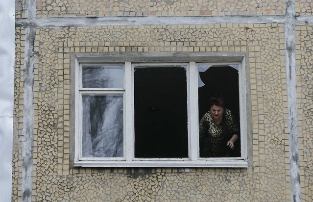 A woman looks out of the window of a residential block damaged by a shelling in Donetsk, eastern Ukraine, February 1, 2015. (Photo by Maxim Shemetov/Reuters)