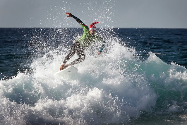 A man wearing a Santa hat practices surf at the beach of Las Americas on the Spanish Canary Island of Tenerife on December 11, 2012. (Photo by Desiree Martin/AFP Photo)