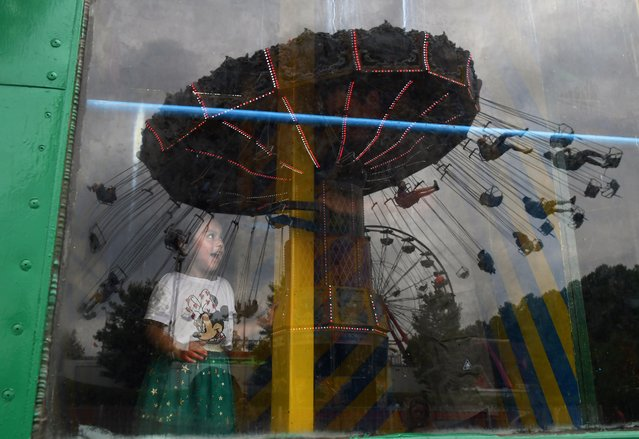 Emily Barroso, 3, watches people on the Wave Swinger ride reflected on a window of Lily's Storyland attraction at a carnival during the Celebrate Fairfax festival in Fairfax, Va. on June 15, 2018. (Photo by Matt McClain/The Washington Post)