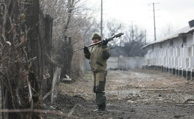 A member of a rebel unit of the self-proclaimed separatist Donetsk People's Republic re-adjusts his rifle in the village of Olenivka, south of Donetsk, February 7, 2015. (Photo by Maxim Shemetov/Reuters)