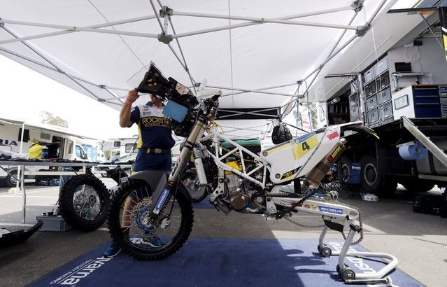 A mechanic works on the Husqvarna motorcycle of Pablo Quintanilla of Chile outside the technical verification area ahead of the Dakar Rally 2016 in Buenos Aires, Argentina, December 31, 2015. (Photo by Marcos Brindicci/Reuters)