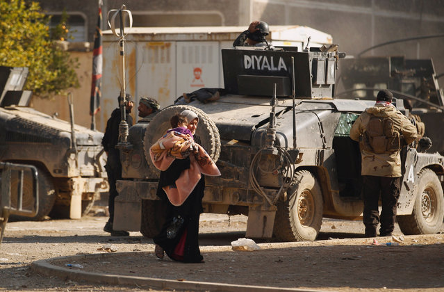 A woman carrying her child walks next to vehicles of Iraqi Special Operations Forces (ISOF) during a battle with Islamic State militants in Mosul, Iraq, November 28, 2016. (Photo by Khalid al Mousily/Reuters)