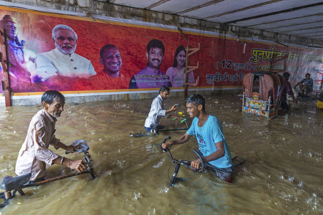 In this Sunday, August 12, 2018, photo,  commuters make their way through a railway under pass where  posters of Indian Prime Minister Narendra Modi, left and Uttar Pradesh Chief Minister Yogi Aditya Nath are displayed following heavy rains in Allahabad, India. India gets its monsoon rains from June to September. (Photo by Rajesh Kumar Singh/AP Photo)