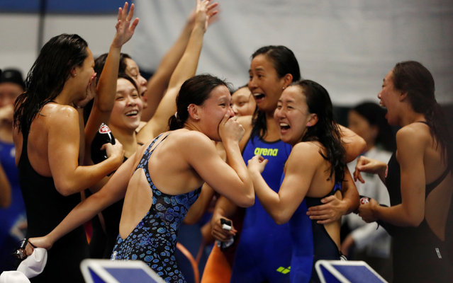Swimmers from Hong Kong (black) and Singapore (blue) celebrate after the final of the women's 4x100 m medley relay swimming event during the 2018 Asian Games in Jakarta on August 23, 2018. (Photo by Jeremy Lee/Reuters)