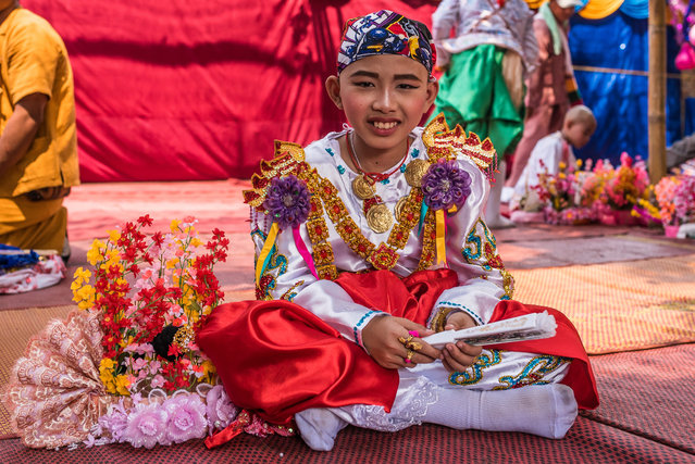 A young boy smiles for the camera as he waits for the festivities to start in the temple in Mae Hong Son, Thailand, April 2016. (Photo by Claudio Sieber/Barcroft Images)