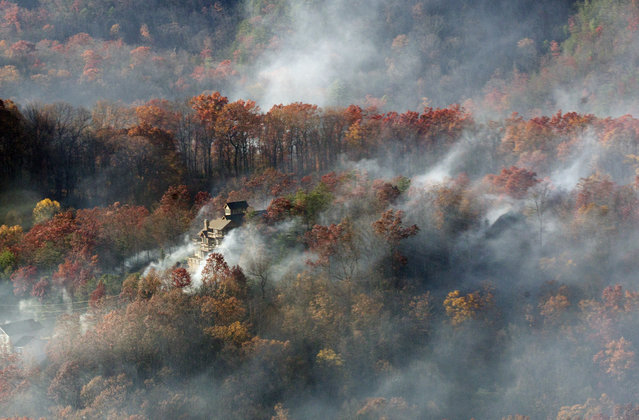 Smoke surrounds a home as seen from aboard a National Guard helicopter near Gatlinburg, Tenn., Tuesday, November 29, 2016. Thousands of people have fled deadly wildfires that have destroyed hundreds of homes and a resort in the Great Smoky Mountains. (Photo by Erik Schelzig/AP Photo)