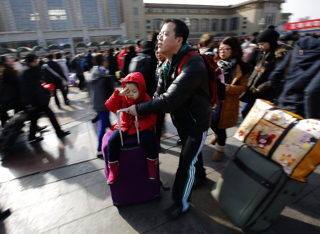 A man carries his daughter on his luggage case at a railway station in Beijing February 16, 2015. (Photo by Kim Kyung-Hoon/Reuters)
