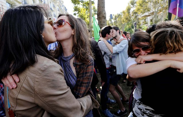 Activists kiss during a demonstration in front of the Russian embassy in Paris, on September 8, 2013. About a dozen gay rights supporters carried placards and chanted slogans outside the Russian embassy to protest Moscow's policies on homosexuality. (Photo by Jacques Brinon/Associated Press)