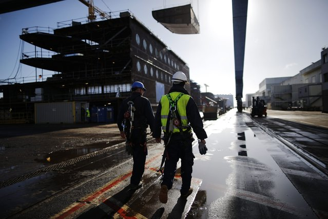 Ship builders walk past a section of the Oasis Class 3 cruise ship under construction at the STX Les Chantiers de l'Atlantique shipyard site in Saint-Nazaire, western France, February 17, 2015. (Photo by Stephane Mahe/Reuters)