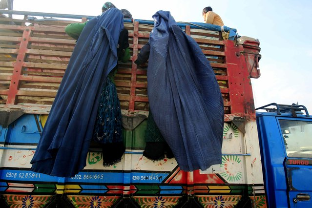 Afghan refugee women, clad in a burqa, climb on a truck to be repatriated to Afghanistan, at the United Nations High Commissioner for Refugees (UNHCR) office on the outskirts of Peshawar February 13, 2015. (Photo by Fayaz Aziz/Reuters)