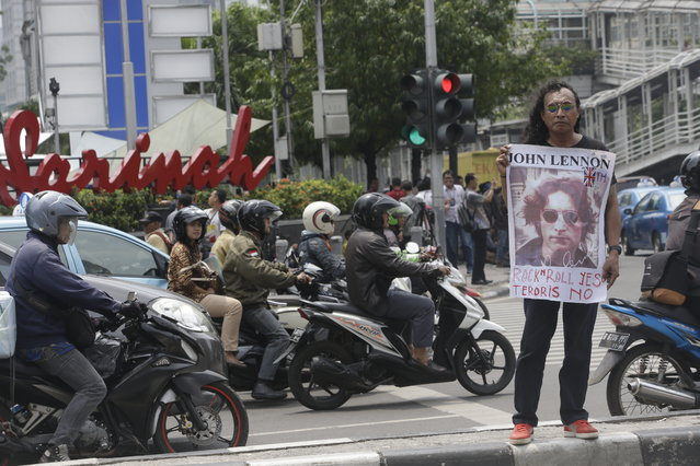 A man stands on a traffic median with a poster of John Lennon across the street from Sarinah shopping mall near the Starbucks cafe where Thursday's attack occurred in Jakarta, Indonesia, Friday, January 15, 2016. (Photo by Tatan Syuflana/AP Photo)