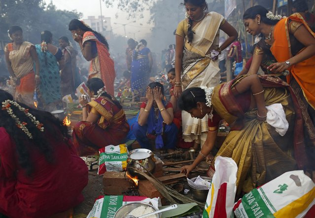 A devotee reacts to smoke as others prepare ritual rice dishes to offer to the Hindu Sun God as they attend Pongal celebrations at a slum in Mumbai, India, January 15, 2016. (Photo by Danish Siddiqui/Reuters)