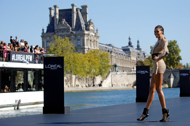A model Cindy Bruna presents a creation on a giant catwalk installed on a barge on the Seine River during a public event organized by French cosmetics group L'Oreal as part of Paris Fashion Week, France, September 30, 2018. (Photo by Stephane Mahe/Reuters)