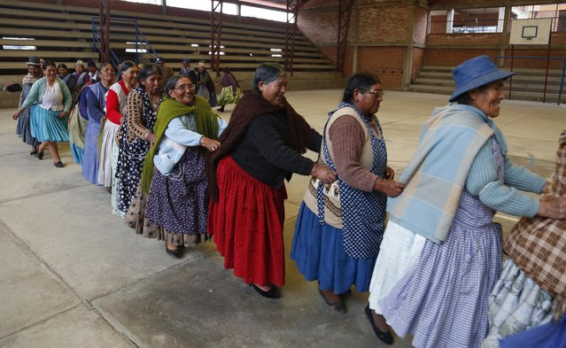 """In this January 28, 2105 photo, elderly Aymara indigenous women hold on to each other as they run laps to warm up for a handball game in El Alto, Bolivia. The grandmothers, known in the Aymara language as """"Awichas"""", warm-up with exercises while singing a childhood song. (Photo by Juan Karita/AP Photo)"""