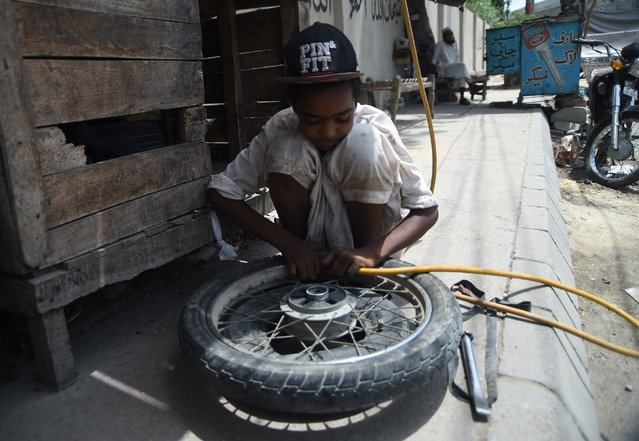 A Pakistani young boy fills air in a tyre at a roadside shop in Karachi on June 12, 2018 on the World Day Against Child Labour. (Photo by Rizwan Tabassum/AFP Photo)