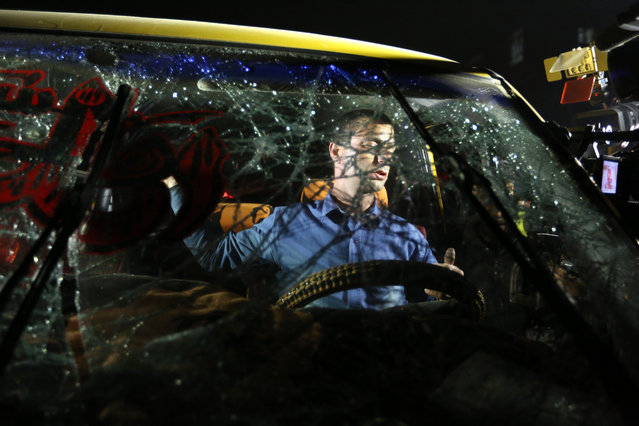 An Afghan driver is seen through the shattered windshield of a car at the site of a suicide attack near the Russian embassy in Kabul, Afghanistan, Wednesday, January 20, 2016. A suicide car bomb attack close to the Russian embassy in the capital, Kabul, has killed many people and wounded more than a dozen, an Afghan official said Wednesday. (Photo by Rahmat Gul/AP Photo)