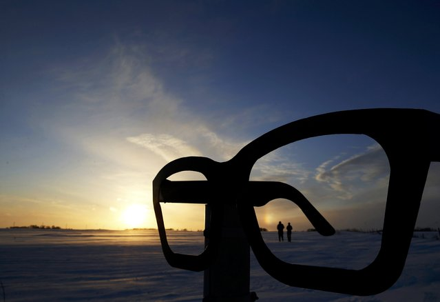 Visitors to the Buddy Holly crash site are framed by a giant tribute to the singer's glasses in Clear Lake, Iowa, United States, January 16, 2016. Holly died in a plane crash in the corn field in 1959. (Photo by Jim Young/Reuters)