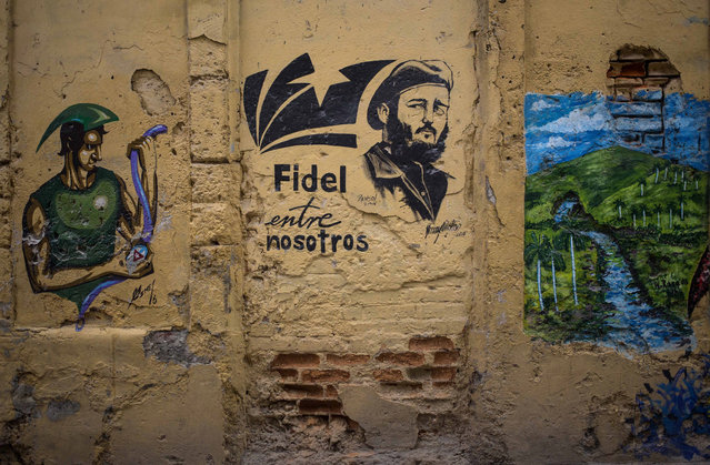 """In this August 13, 2018 photo, she Spanish message: """"Fidel is among us"""" covers a wall next to an image of the late leader in Havana, Cuba. Cuba's new constitution is being debated among citizens until November 15, and any revisions accepted by the government will be included in the final document to be presented in a referendum in 2019. (Photo by Desmond Boylan/AP Photo)"""