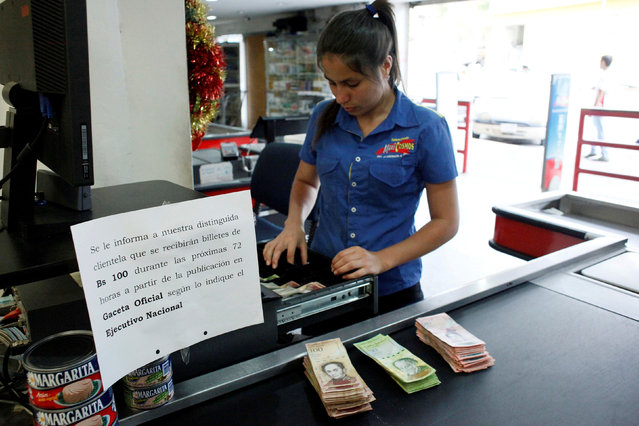 "A cashier counts Venezuelan bolivar notes at a supermarket checkout line in San Cristobal, Venezuela, December 12, 2016. The placard reads: ""We inform our distinguished clientele that 100 bolivar notes will be received during the next 72 hours from the date of publication in the Official Gazette as indicated by the National Executive"". (Photo by Carlos Eduardo Ramirez/Reuters)"