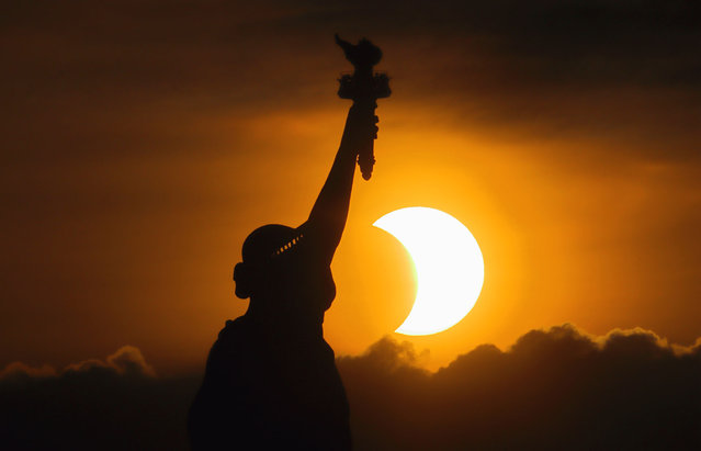 """The sun rises next to the Statue of Liberty during an annular eclipse on June 10, 2021 in New York City. Northeast states in the U.S. saw a rare eclipsed sunrise, while in other parts of the Northern Hemisphere, this annular eclipse will be seen as a visible thin outer ring of the sun's disk that is not completely covered by the smaller dark disk of the moon, a so-called """"ring of fire"""".    (Photo by Gary Hershorn/Getty Images)"""