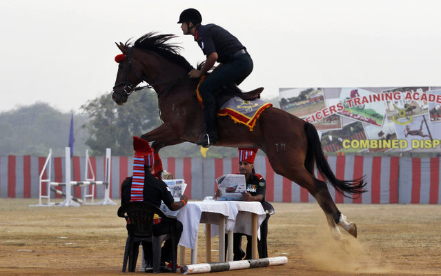 An Indian Army soldier takes a horse over a jump at a combined display with trainees from the Officers Training Academy (OTA) in Chennai, India, Friday, March 13, 2015. A total of 185 cadets will be passing out from the OTA on Saturday. (Photo by Arun Sankar K./AP Photo)