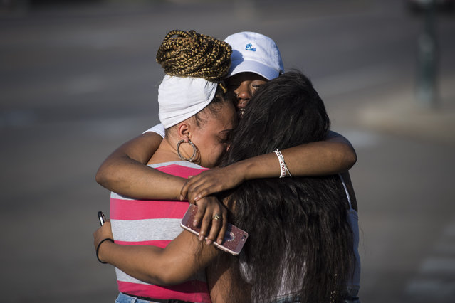 Allysza Castile, the younger sister of Philando Castile, center, is hugged by her best friends near a roadside vigil where Castile was fatally shot in Falcon Heights, Minn. on Saturday July 09, 2016. Philando Castile was shot and killed after a traffic stop by police in Falcon Heights, Wednesday night. A video shot by Diamond Reynolds of the shooting went viral. (Photo by Jabin Botsford/The Washington Post)