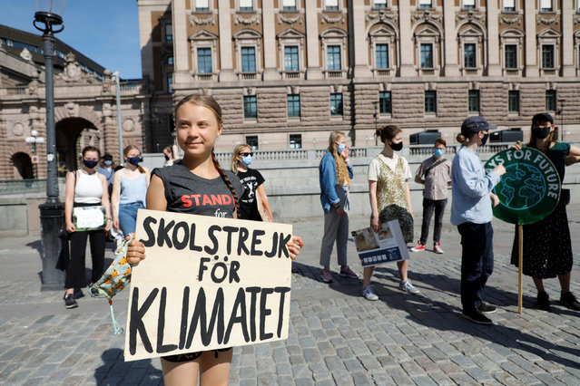 """Swedish climate activist Greta Thunberg and other activists gather for a protest against climate change in front of the Swedish parliament building in Stockholm on July 2, 2021. Swedish climate activist Greta Thunberg launched a new broadside on July 1 against """"role-playing"""" by political and economic leaders over the climate crisis, accusing them of using it as a business opportunity. Thunberg, 18, derided wealthy nations' climate commitments as """"vastly insufficient"""" in the face of """"more and more extreme weather events, raging all around us"""". (Photo by Christine Olsson/TT News Agency/AFP Photo)"""