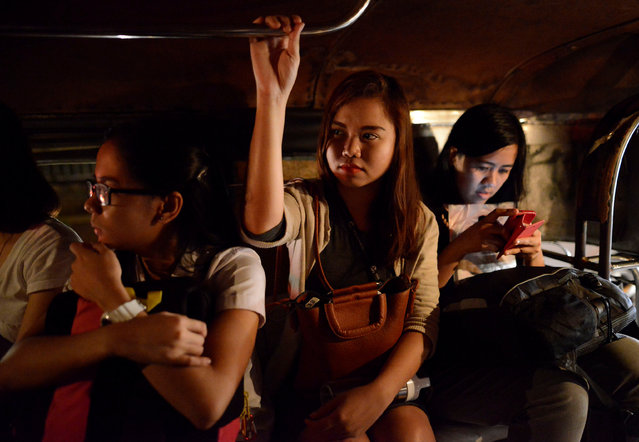 "Cristine Angelie Garcia (C), 24, rides a jeepney on her way to work at a call centre for the midnight shift in Taguig city, Metro Manila, Philippines October 3, 2016. ""Maybe there is another way where people do not need to die"", she said, adding she felt safer walking the streets at night. ""I'm on Duterte's side. Maybe he's just misunderstood because he grew up on the streets"". (Photo by Ezra Acayan/Reuters)"
