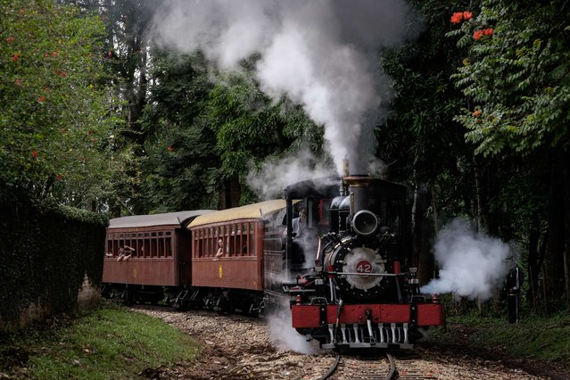 "The ""Maria Fumaca"" (Smoking Mary) steam train arrives at the station in Tiradentes, Minas Gerais State, Brazil, on March 22, 2015. The steam train, made by the Baldwin Locomotive Works of Philadelphia, US, makes a trip for tourist between Tiradentes and Sao Joao del Rei, about 13 km distance, on Fridays, Saturdays and Sundays. (Photo by Yasuyoshi Chiba/AFP Photo)"
