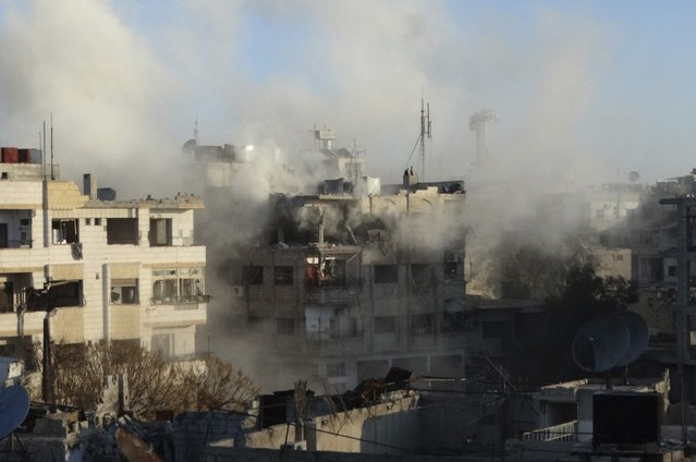 Smoke rises from damaged buildings during what activists said were clashes between Free Syrian Army fighters and the forces of Syria's President Bashar al-Assad in Jobar, a suburb of Damascus January 4, 2015. (Photo by Msallam Abd Albaset/Reuters)