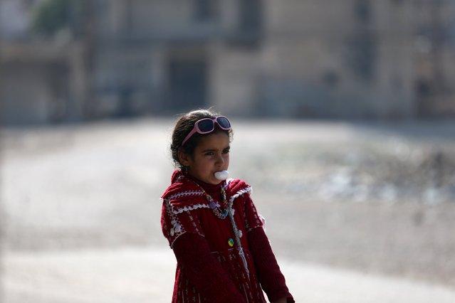 A girl blows a bubble gum on a street in Douma, Syria February 3, 2016. (Photo by Bassam Khabieh/Reuters)