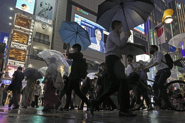 In this July 8, 2021, file photo, pedestrians walk past a giant public TV with a live broadcast of a news conference by Japanese Prime Minister Yoshihide Suga after he announced a state of emergency because of rising coronavirus infections in Tokyo. Faced with rapidly rising numbers of new coronavirus infections and growing concern over the proliferation of the highly contagious delta variant, major Asia-Pacific cities implemented new restrictions Friday, July 2021, in the hope of reversing the trend before health care systems are overwhelmed. (Photo by Eugene Hoshiko/AP Photo)