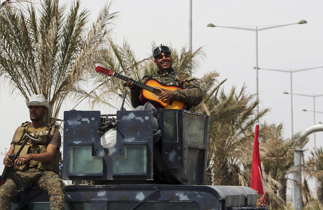 An Iraqi soldier plays his guitar atop his armored vehicle on the main road between Baghdad and Tikrit, 80 miles (130 kilometers) north of Baghdad, Iraq, Friday, April 3, 2015. (Photo by Khalid Mohammed/AP Photo)