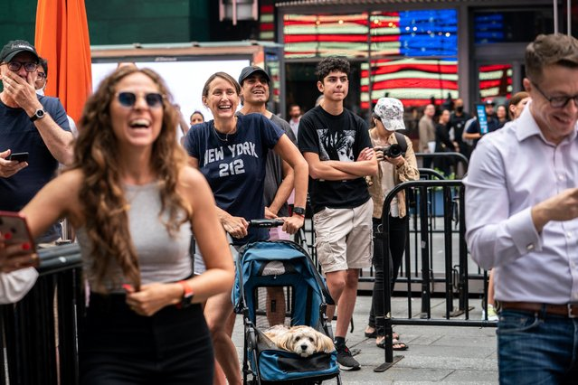 People watch the launch of billionaire American businessman Jeff Bezos and his three crew-mates on Blue Origin's inaugural flight to the edge of space, on a screen in Times Square in New York City, U.S., July 20, 2021. (Photo by Jeenah Moon/Reuters)
