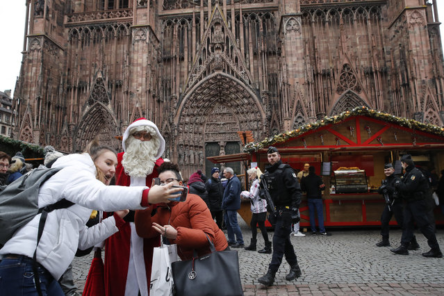 People take a selfie with man dressed like a Santa Claus as police officers patrol outside the cathedral in Strasbourg, eastern France, Friday, December 14, 2018. The man authorities believe killed three people during a rampage near a Christmas market in Strasbourg died Thursday in a shootout with police at the end of a two-day manhunt, French authorities said. (Photo by Christophe Ena/AP Photo)
