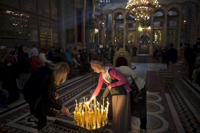 Christian worshippers light candles in the Church of the Holy Sepulchre in Jerusalem's Old City April 5, 2015. (Photo by Ronen Zvulun/Reuters)