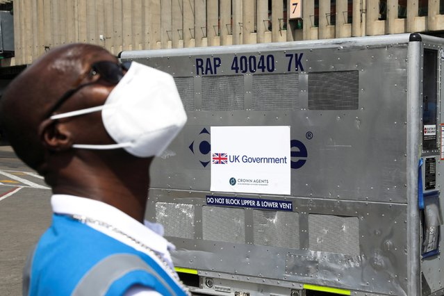 A health official stands next to a refrigerated container holding a shipment of more than 400,000 doses of the AstraZeneca/Oxford coronavirus disease (COVID-19) vaccine, donated to Kenya by the the British government, at the Jomo Kenyatta International Airport in Nairobi, Kenya, July 31, 2021. (Photo by Baz Ratner/Reuters)