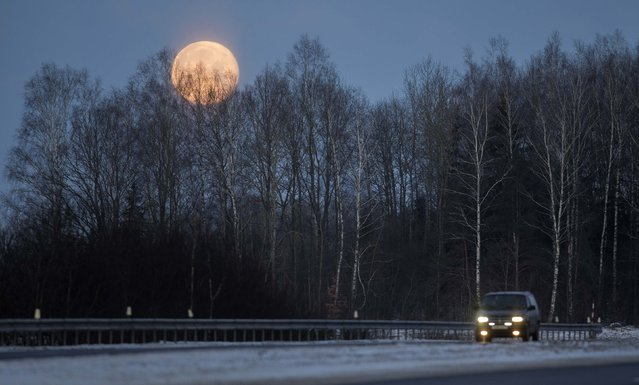 A full moon is seen over the forest as a car drives near the village of Pershai, west of Minsk, January 6, 2015. (Photo by Vasily Fedosenko/Reuters)