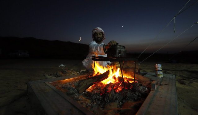 An Emirati heats a tea pot over an open fire at the Liwa desert, 220 kms west of Abu Dhabi, on the sidelines of the Mazayin Dhafra Camel Festival on December 21, 2013. (Photo by Karim Sahib/AFP Photo)