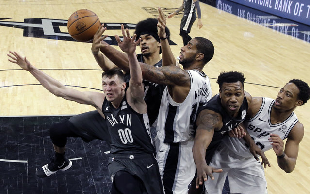 San Antonio Spurs center LaMarcus Aldridge (12) battles Brooklyn Nets forward Rodions Kurucs (00) and center Jarrett Allen, second from left, for a rebound during the second half of an NBA basketball game, in San Antonio, Thursday, January 31, 2019. San Antonio won 117-114. (Photo by Eric Gay/AP Photo)