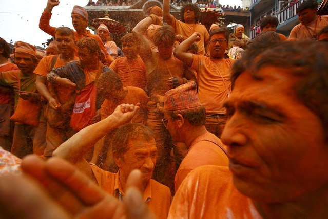 Devotees throw vermillion powder on one another to celebrate the Nepali New Year, also known as Sindoor Jatra, at Thimi, in Bhaktapur April 15, 2015. (Photo by Navesh Chitrakar/Reuters)