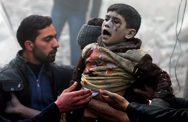 Men help a wounded boy who survived what activists say was an air strike by forces loyal to Syrian President Bashar al-Assad in the Duma neighborhood of Damascus, on January 7, 2014. (Photo by Bassam Khabieh/Reuters)