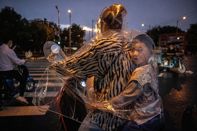 A boy sits inside his mother's plastic raincoat as they wait to cross at a traffic light during a rainstorm on September 8, 2021 in Beijing, China. While cases were relatively low compared to many countries, China has recently contained a COVID-19 outbreak of the highly contagious Delta variant. (Photo by Kevin Frayer/Getty Images)
